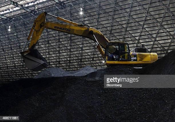 A Komatsu Ltd excavator sits inside a coal storage yard at the Joban Joint Power Co Nakoso coalfired power station in Iwaki City Fukushima Prefecture...