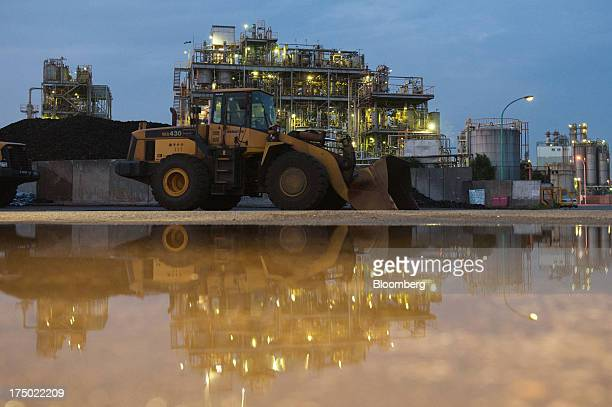 Komatsu Ltd. WA430 wheel loader standing in front of a chemical plant is reflected in a puddle at dusk in the Keihin industrial area of Kawasaki...