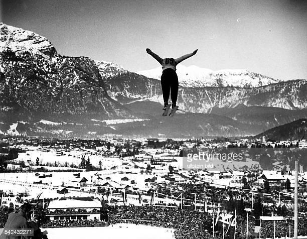 Kombinierter Sprunglauf Ein Teilnehmer springtvon der Schanze am Gudiberg ins Stadiondahinter liegt Partenkirchen und dasGebirgspanorama Februar 1936