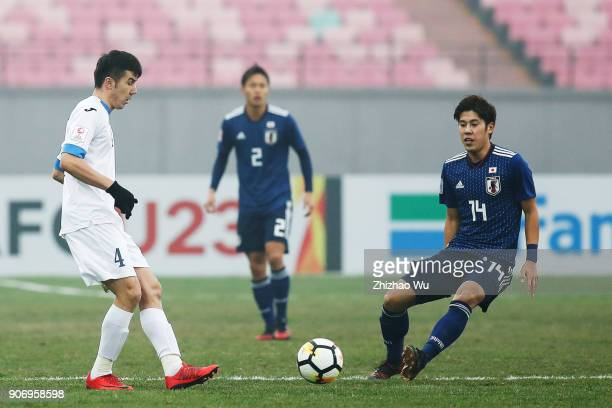 Komilov Akramjon of Uzbekistan and Takagi Akito of Japan in action during AFC U23 Championship Quarterfinal between Japan and Uzbekistan at Jiangyin...