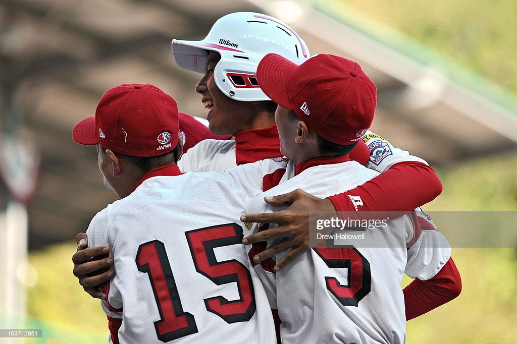 Konan Tomori #28 of the Japan Little League team is hugged by teammates Ryota Norimatsu #15 and Takeshi Saito after hitting a two run homerun in the top of the sixth inning durng the game against the United States on August 29, 2010 in South Willamsport, Pennsylvania. Japan went on to win the Little League World Series Championship 4-1.