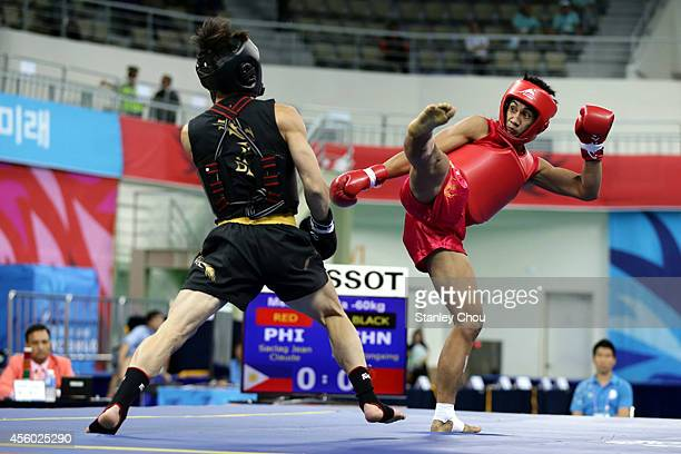 Kong Hongxing of China and Saclag Jean Claude of the Philippines competes during the Men's Sanda60kg Wushu Final during day five of the 2014 Asian...