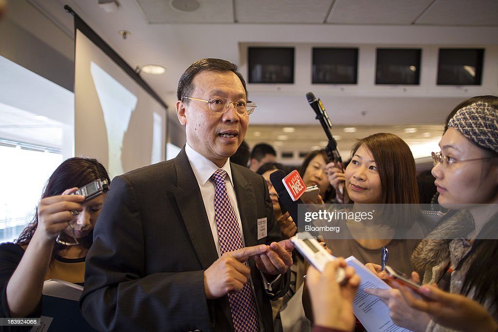 Kong Qingping, chairman of China Overseas Land & Investment Ltd., second left, speaks to members of the media following a news conference in Hong Kong, China, on Monday, March 18, 2013. China Overseas Land & Investment Ltd., the country's biggest developer by market value listed in Hong Kong, said 2012 profit climbed 21 percent on gains from property revaluations and the sales of stakes in some projects. Photographer: Jerome Favre/Bloomberg via Getty Images