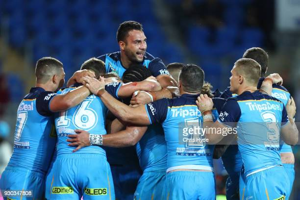 Konrad Hurrell of the Titans celebrates with team mates after scoring a try to win the round one NRL match between the Gold Coast Titans and the...
