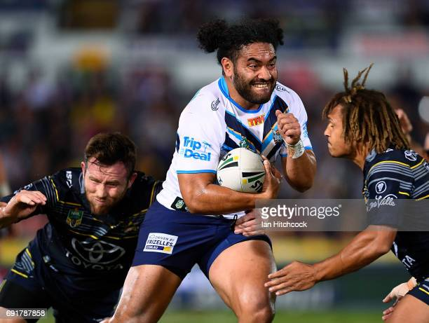 Konrad Hurrell of the Titans is tackled by Gavin Cooper and Ray Thompson of the Cowboys during the round 13 NRL match between the North Queensland...