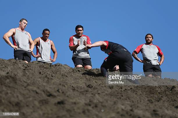 Konrad Hurrell of the Warriors encourages his team mate as they train on the sand dunes during the New Zealand Warriors NRL training session at...