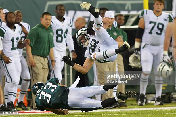 Konrad Reuland of the New York Jets gets upended by Emmanuel Acho of the Philadelphia Eagles at MetLife Stadium on August 29 2013 in East Rutherford...
