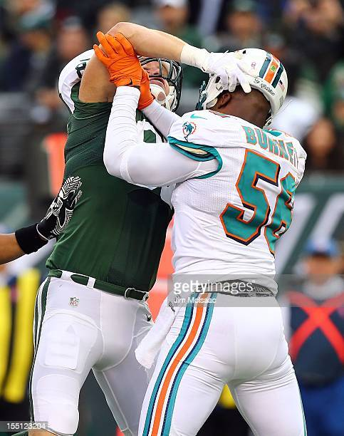 Konrad Reuland of the New York Jets mixes it up with Kevin Burnett of the Miami Dolphins during the first half at MetLife Stadium on Sunday October...