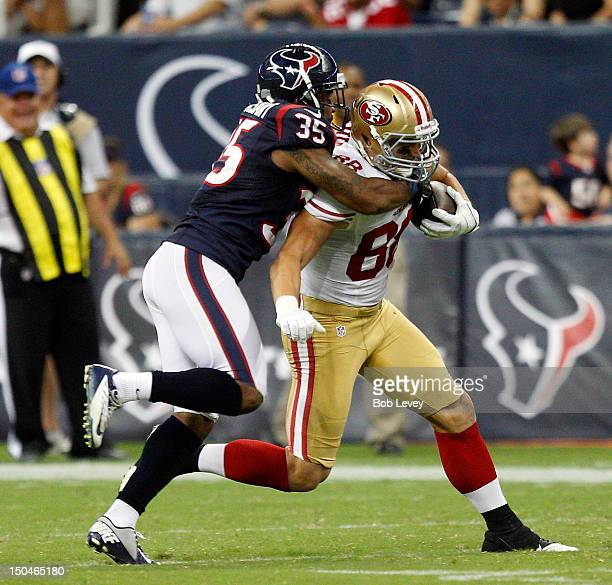 Konrad Reuland of the San Francisco 49ers is tackled by Eddie Pleasant of the Houston Texans after completing a reception at Reliant Stadium on...