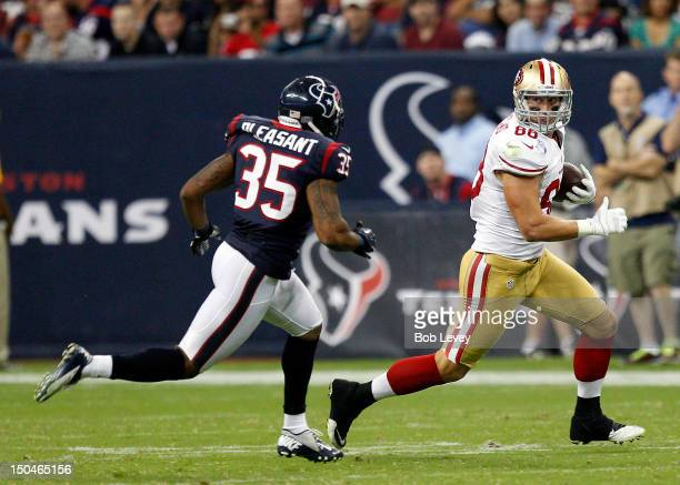 Konrad Reuland of the San Francisco 49ers races away from Eddie Pleasant of the Houston Texans after completing a reception at Reliant Stadium on...