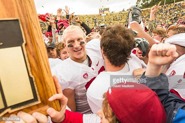Konrad Reuland of the Stanford Cardinal celebrates with quarterback Andrew Luck and the Stanford Axe following the 113th Big Game between the...