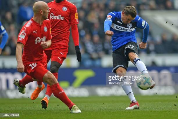Konstantin Kerschbaumer of Bielefeld kicks the ball past Patrick Herrmann of Kiel during the Second Bundesliga match between DSC Arminia Bielefeld...
