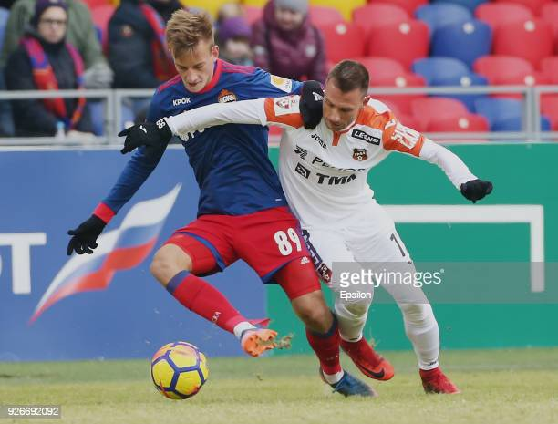 Konstantin Kuchaev of PFC CSKA Moscow vies for the ball with Nikolay Dimitrov of FC Ural Ekaterinburg during the Russian Premier League match between...