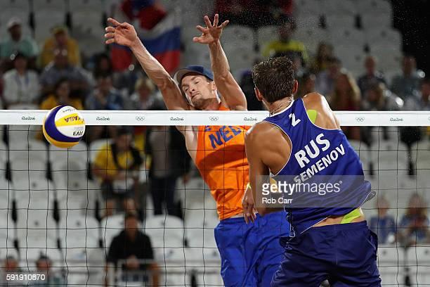 Konstantin Semenov of Russia and Robert Meeuwsen of Netherlands battle at the net during the Men's Beach Volleyball Bronze medal match at the Beach...