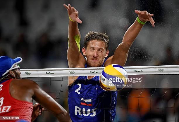 Konstantin Semenov of Russia blocks a shot from Reynaldo Gonzalez Bayard of Cuba during the Men's Beach Volleyball Quarterfinal match between the...