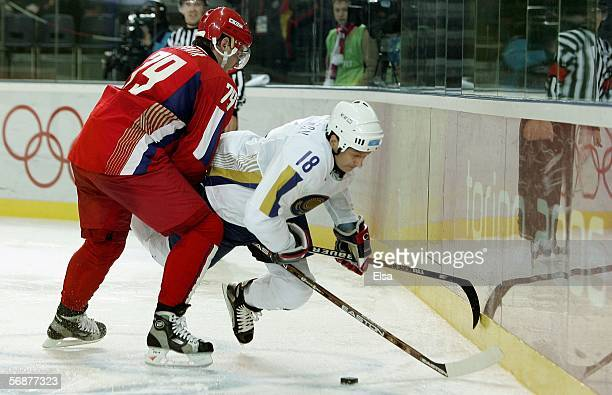 Konstantin Shafranov of Kazakhstan pursues the puck against the defense of Alexei Yashin of Russia during the men's ice hockey Preliminary Round...