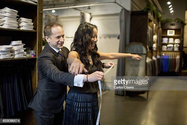 TORONTO ON DECEMBER Konstantine Malishevski the made to measure manager of GotStyle demonstrate how he measures women on Melissa Austria the owner of...