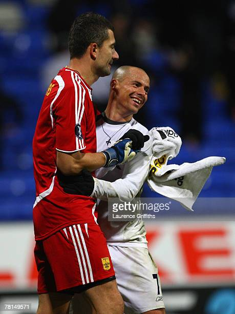 Konstantinos Chalkias of Aris Thessaloniki and Stelios of Bolton Wanderers embrace at the end of the UEFA Cup Group F match between Bolton Wanderers...