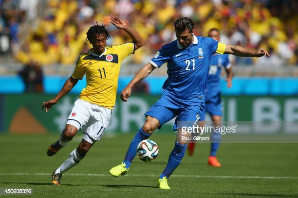 Konstantinos Katsouranis of Greece controls the ball against Juan Guillermo Cuadrado of Colombia during the 2014 FIFA World Cup Brazil Group C match...