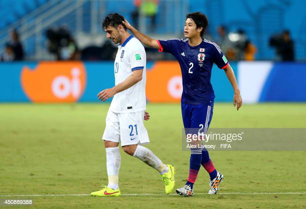 Konstantinos Katsouranis of Greece is consoled by Atsuto Uchida of Japan while walking off the pitch after receiving a red card during the 2014 FIFA...