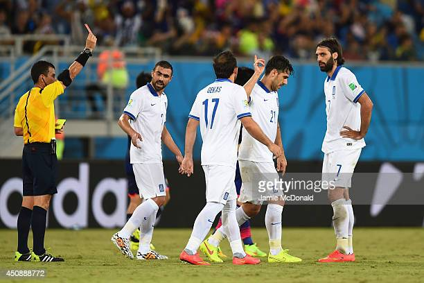 Konstantinos Katsouranis of Greece is shown a red card after receiving his second yellow by referee Joel Aguilar during the 2014 FIFA World Cup...
