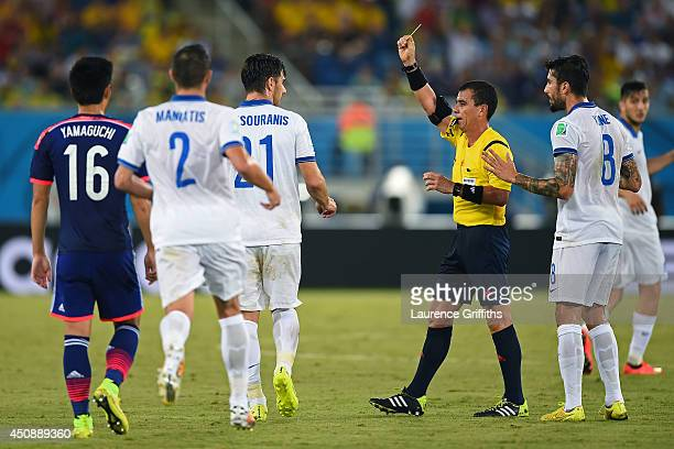 Konstantinos Katsouranis of Greece is shown his second yellow card resulting in a red card by referee Joel Aguilar during the 2014 FIFA World Cup...