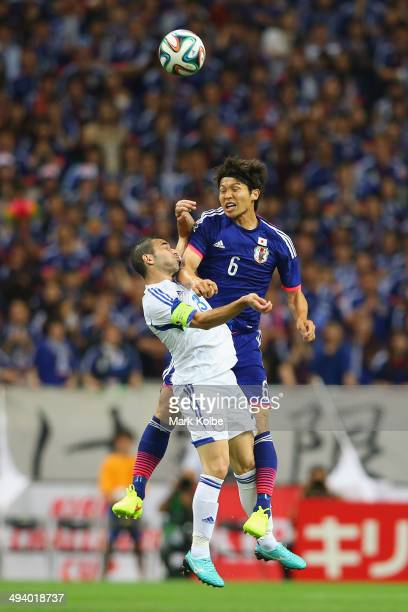 Konstantinos Makridis of Cyprus and Masato Morishige of Japan compete for the ball in the air during the Kirin Challenge Cup international friendly...