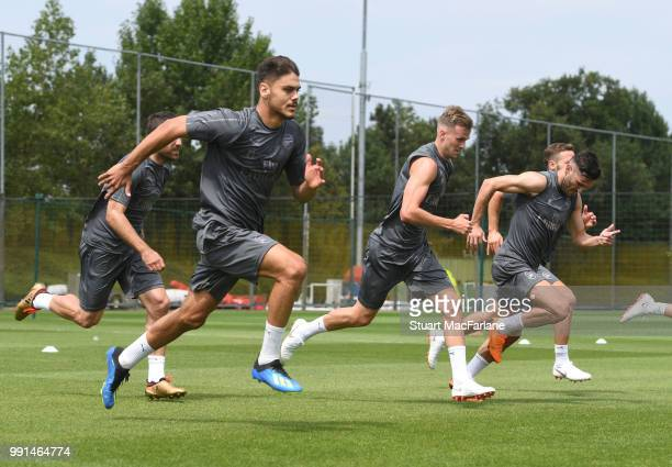Konstantinos Mavropanos and Rob Holding of Arsenal runs during a training session at London Colney on July 4 2018 in St Albans England