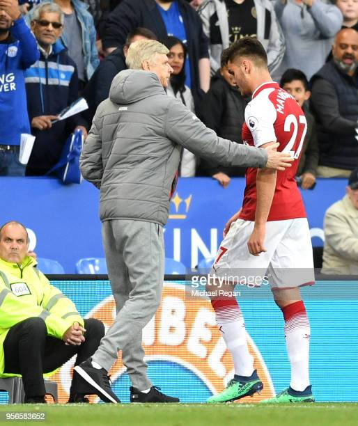 Konstantinos Mavropanos of Arsenal walks off dejected after being sent off as Arsene Wenger Manager of Arsenal pats him on the back during the...
