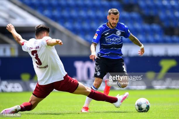 Konstantinos Mavropanos of Nurnberg tackles Jonathan Clauss of Arminia Bielefeld during the Second Bundesliga match between DSC Arminia Bielefeld and...