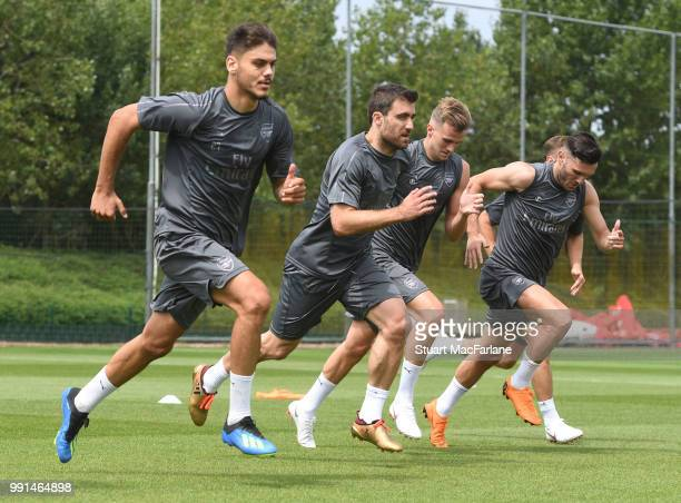 Konstantinos Mavropanos Sokratis Papastathopolus Rob Holding and Lucas Perez of Arsenal runs during a training session at London Colney on July 4...