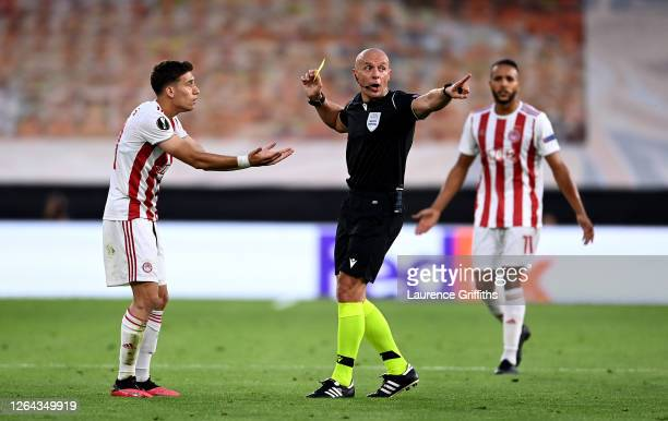 Konstantinos Tsimikas of Olympiacos is shown a yellow card by referee Szymon Marciniak during the UEFA Europa League round of 16 second leg match...