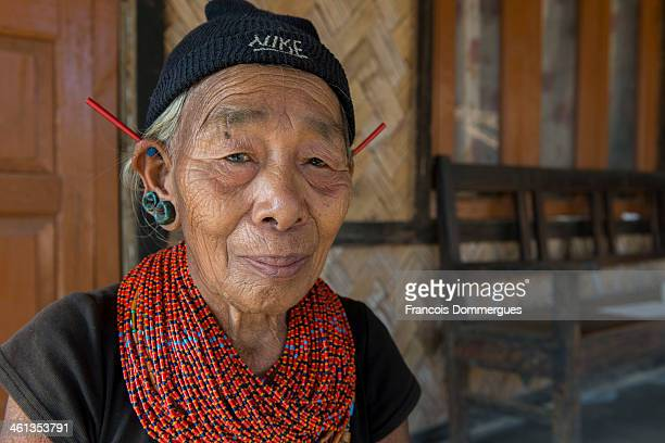 Konyak ladies traditionally wear colorful necklaces and a number of earrings, including long red-orange antenna-like spikes.