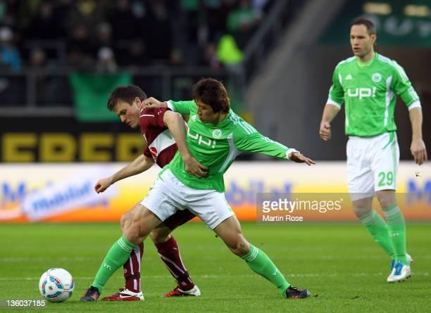 Koo Ja Cheol of Wolfsburg and William Kvist of Stuttgart battle for the ball during the Bundesliga match between VfL Wolfsburg and VfB Stuttgart at...