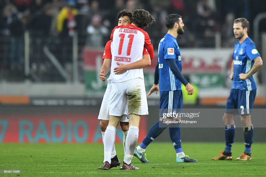Koo Ja-cheol of Augsburg (behind) and Michael Gregoritsch of Augsburg embrace after the Bundesliga match between FC Augsburg and Hamburger SV at WWK-Arena on January 13, 2018 in Augsburg, Germany.