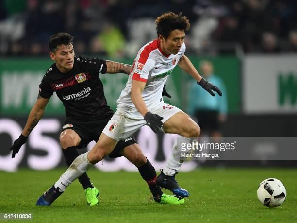 Koo JaCheol of Augsburg is challenged by Charles Aranguiz of Leverkusen during the Bundesliga match between FC Augsburg and Bayer 04 Leverkusen at...