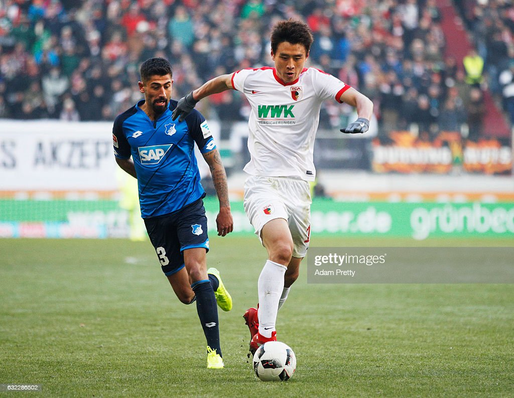 Koo Ja-Cheol of Augsburg is challenged by Kerem Demirbay of 1899 Hoffenheim during the Bundesliga match between FC Augsburg and TSG 1899 Hoffenheim at WWK Arena on January 21, 2017 in Augsburg, Germany.