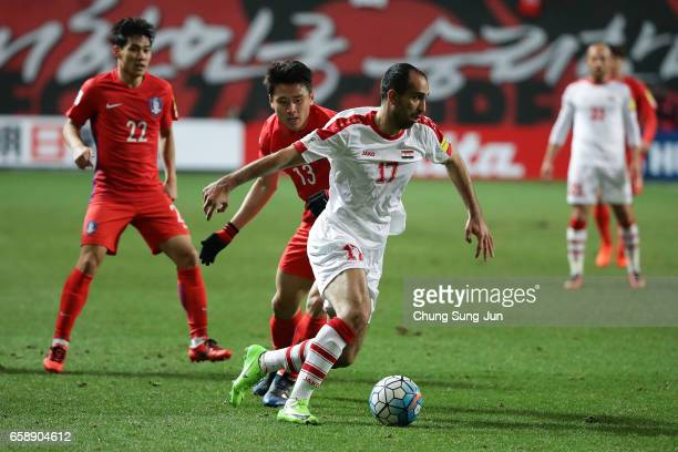 Koo JaCheol of South Korea competes for the ball with Almasri Hadi of Syria during the FIFA World Cup Qualification AFC Final Group Stage match...