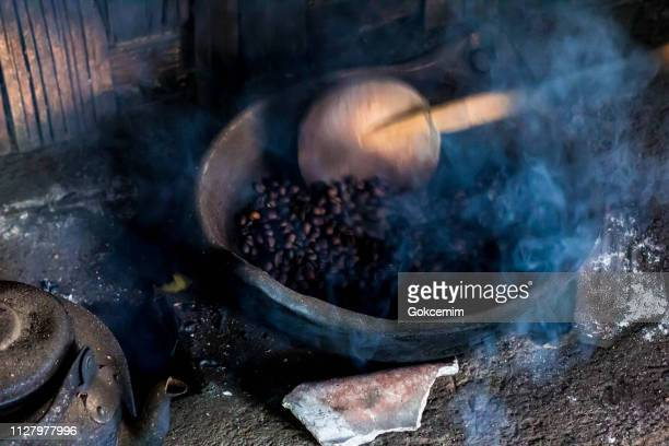 kopi luwak coffee beans in indonesian coffee roastery. old traditional way of roasting raw coffee beans on fire. - bassarisco foto e immagini stock