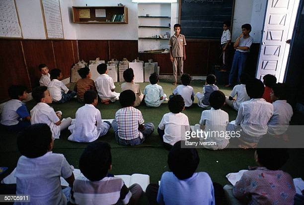 A Koran school where boys learn by memorizing and reciting the Koran off of wooden tablets