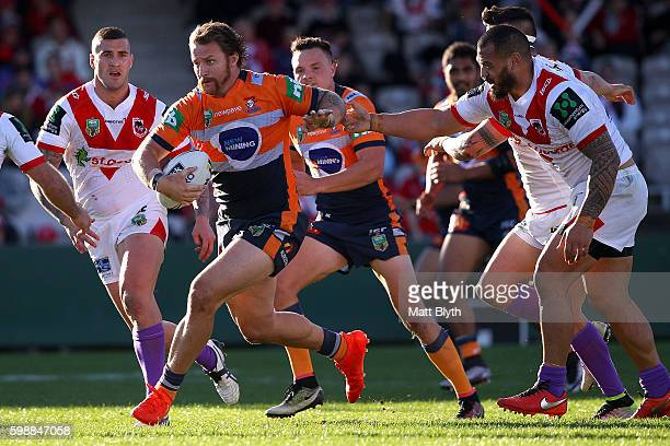 Korbin Sims of the Knights is tackled during the round 26 NRL match between the St George Illawarra Dragons and the Newcastle Knights at WIN Jubilee...