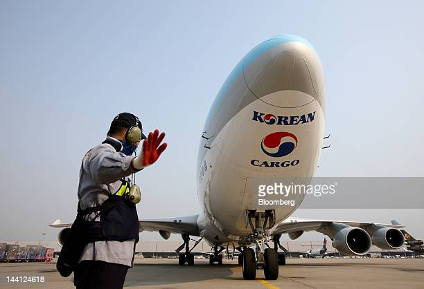 A Korea Airport Service Co staff member directs a Korean Air Lines Co freight plane arriving from China at Korean Air's cargo terminal at Incheon...