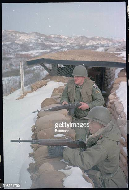 American troops in the demilitarized zone of Korea keep watch over the area from behind sandbag barricades