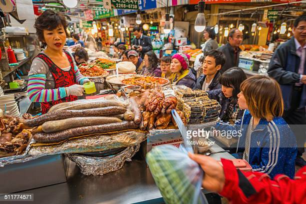 Korea cook and customers at busy market food stall Seoul