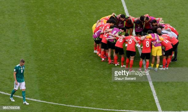 Korea Republic players form a team huddle as Toni Kroos of Germany looks dejected following his sides defeat in during the 2018 FIFA World Cup Russia...