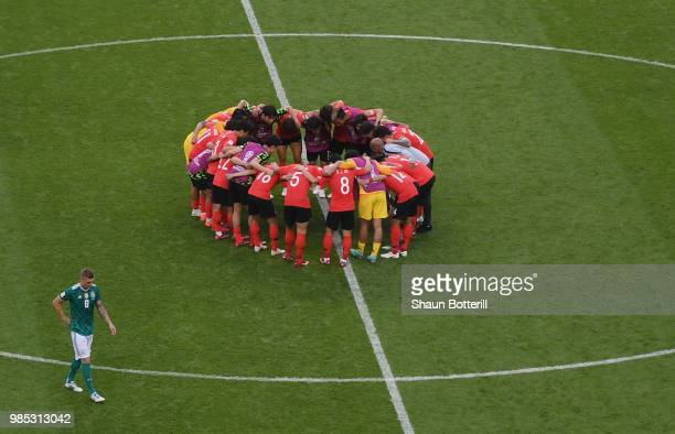 Korea Republic players form a team huddle as Toni Kroos of Germany looks dejected following his sides defeat in the 2018 FIFA World Cup Russia group...