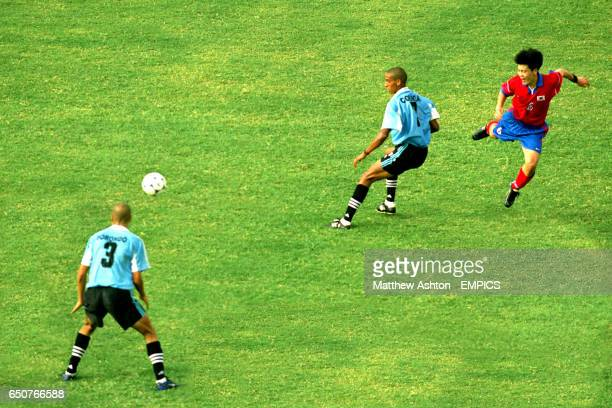 Korea Republic's Chong Gug Song gets his shot past Uruguay's Gonzalo Sorondo and Alejandro Correa Rodriguez