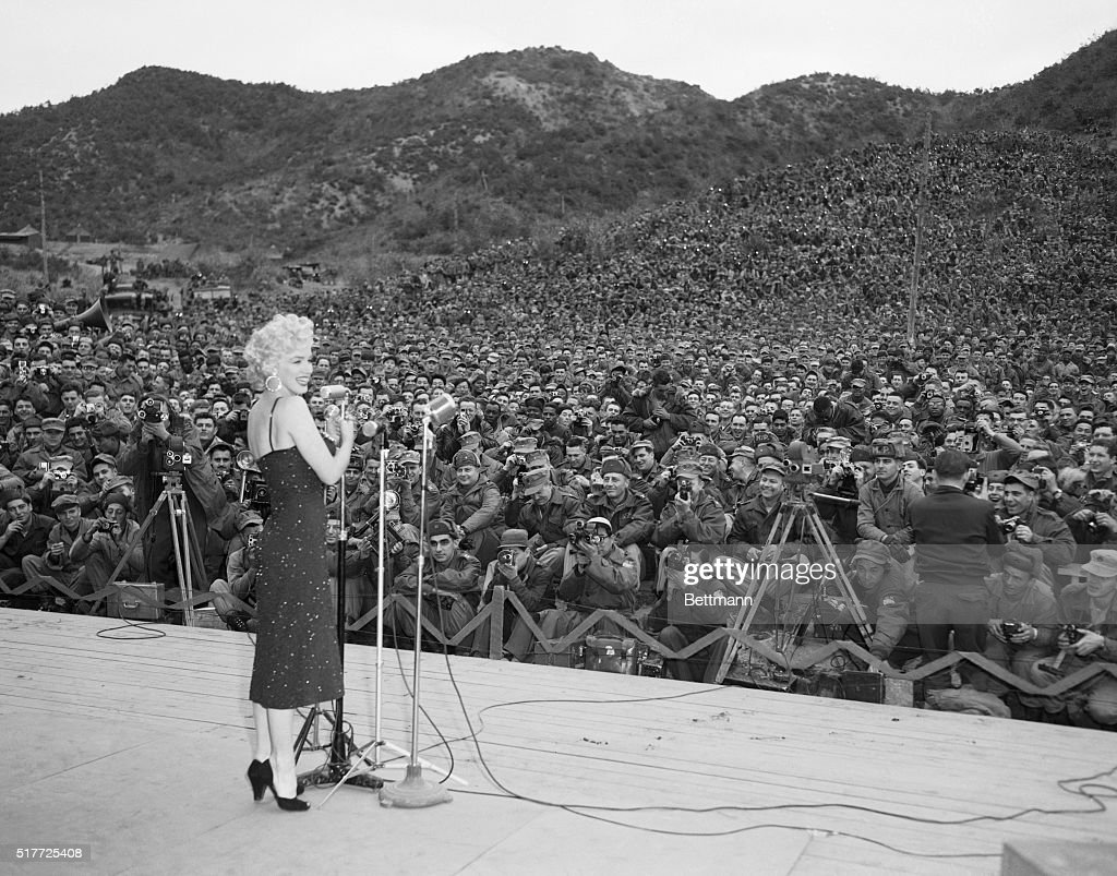 The power of a woman. Over 10,000 GI's turn out to hear and see Marilyn Monroe as the bosomy blonde makes an appearance in Korea, February 16th. Not since President Eisenhower made his pre-inaugural visit has there been such a turnout for a celebrity. The serviceman traveled from all points of the Korea peninsula to get a look at the movie queen.