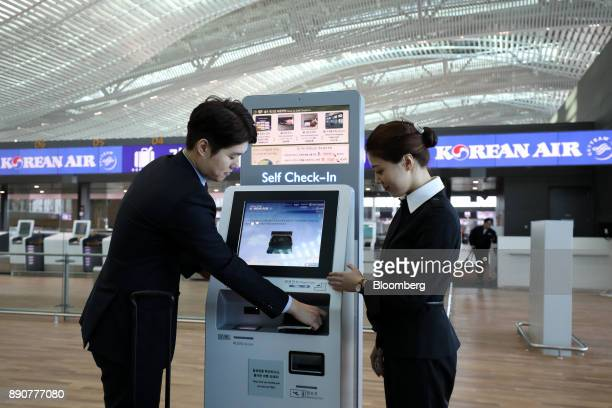 Korean Air Lines Co employees demonstrate a self checkin kiosk inside the nearly completed terminal 2 building during a media preview at Incheon...