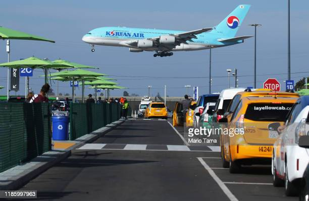 Korean Air plane lands as taxis are lined up at the new 'LAXit' ridehail passenger pickup lot at Los Angeles International Airport on November 6 2019...